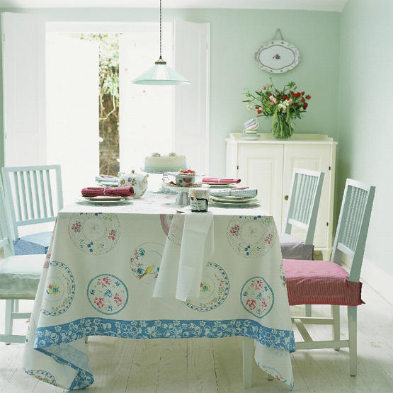 A Light Mint Dining Room With Paneled Shutters And Pale Wood Floors; Simple  Seat Cushion Slipcovers In Different Colors Coordinate With The Tablecloth