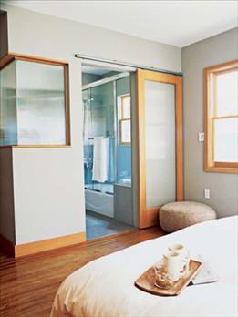 A glass paneled barn door and an internal corner window help fill ...